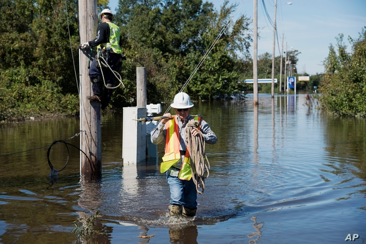 A lineman works to restore power lines near I-95 after the area was flooded by rain from Hurricane Matthew in Lumberton, North Carolina, Oct. 11, 2016.
