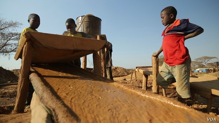 FILE - Two 13-year-old boys and one 15-year-old boy pour crushed gold ore over a sisal sack to concentrate the particles of gold at a processing site in Mbeya Reigon, Tanzania, in this 2013 photo.