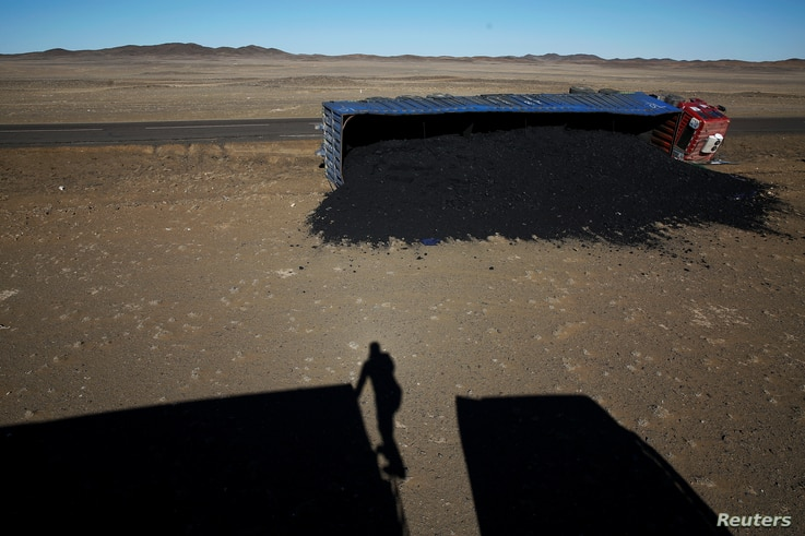 A photographer casts his shadow near a coal truck that flipped over at Khanbogd Soum, near the border with China in the Gobi desert, Mongolia, Oct. 29, 2017. Getting to the border can be a harrowing ordeal, as vehicles speed towards China and back do...