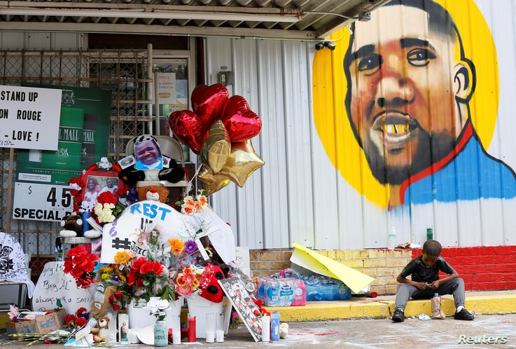 FILE - A boy sits next to a makeshift memorial outside the Triple S Food Mart where Alton Sterling was fatally shot by police in Baton Rouge, Louisiana, July 7, 2016.