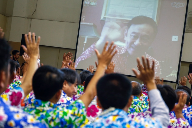 FILE - Opposition Puea Thai party members react as former Thai Prime Minister Thaksin Shinawatra waves to them during a Skype video call at the party headquarters in Bangkok, Thailand, April 7, 2016.