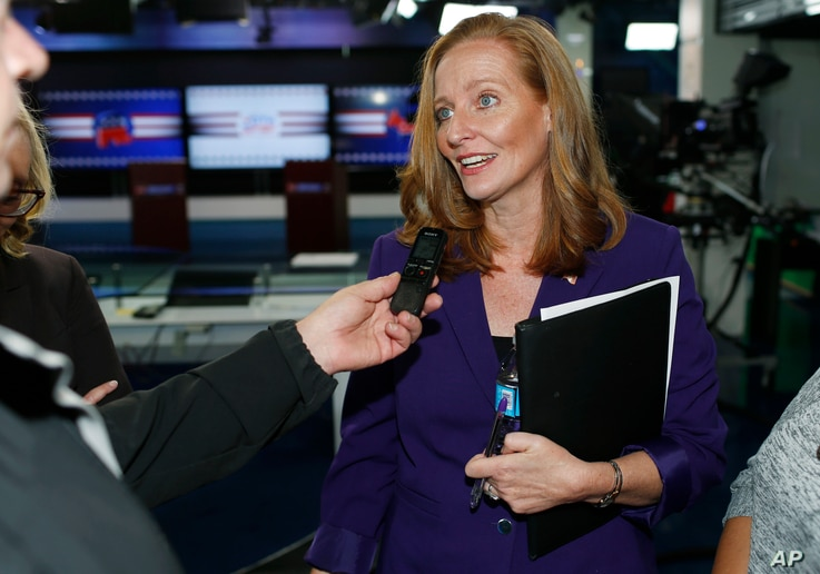 FILE - Democratic candidate for Colorado's 6th Congressional District seat, Morgan Carroll, talks with reporters after debating her opponent, incumbent U.S. Rep. Mike Coffman, at a Spanish language television station in Denver, Oct. 4, 2016.
