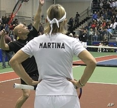 Andre Agassi warms up before tennis fundraiser as Martina Navratilova looks on