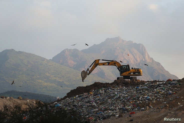 """A mechanic digger works on a waste dump in Til Til, Chile, Aug. 23, 2017. """"With the landfill we lose our identity. People identify us as a trash town,"""" a local said."""