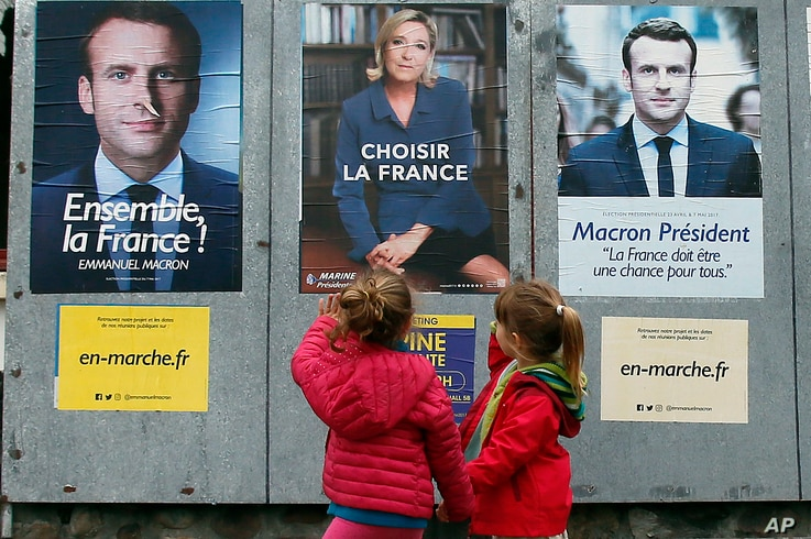 Children walk past election campaign posters for French centrist presidential candidate Emmanuel Macron and far-right candidate Marine Le Pen, in Osses, southwestern France, May 5, 2017. France is voting Sunday in the second round of the presidential...