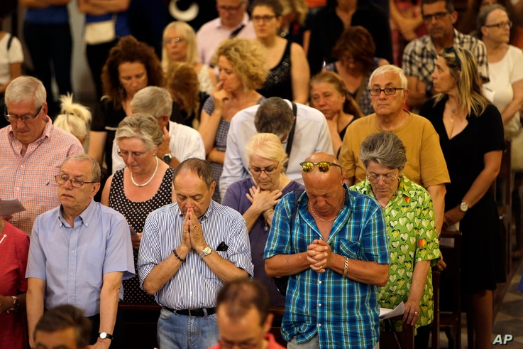 People pray at Sainte-Reparate Cathedral in Nice, France, during a mass in memory of the terrorist attack victims, July 15, 2016.