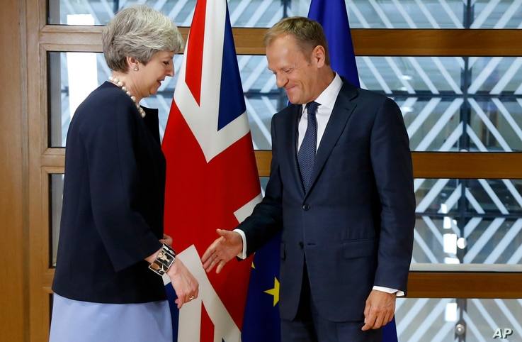 European Council President Donald Tusk, right, reaches out to shake hands with British Prime Minister Theresa May prior to a bilateral meeting on the sidelines of an EU summit in Brussels, June 22, 2017.