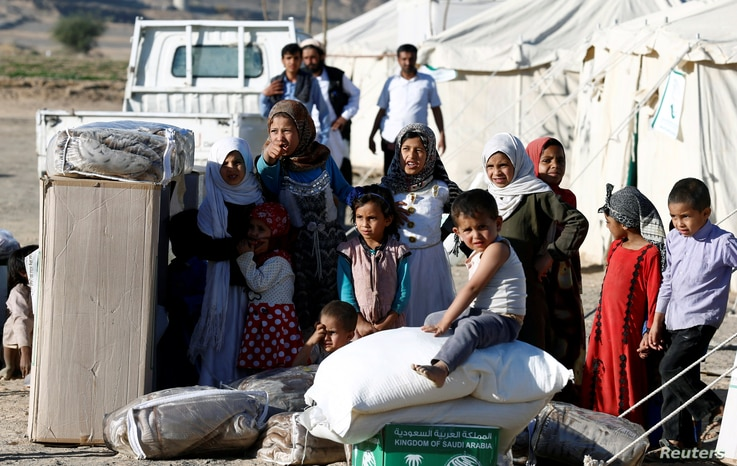 A boy sits on wheat flour as others stand by aid they received from a Saudi distribution center at a camp for internally displaced people (IDPs) near Marib, Yemen, Jan. 26, 2018.