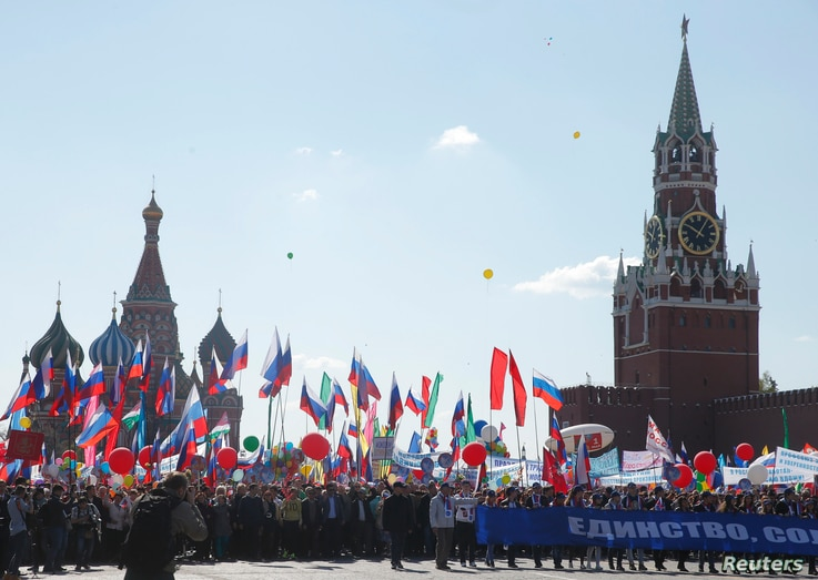 People walk with flags and banners at Red Square during a May Day rally in Moscow, Russia, May 1, 2016.