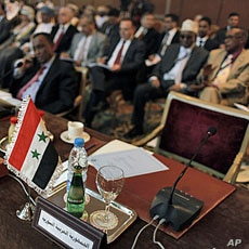 """The Syrian flag and a sign in Arabic that reads, """"the Syrian Arabic Republic,"""" is seen in front of the empty chair of the Syrian representative during the Arab League Syria Group and foreign ministers meeting in Cairo, Egypt Sunday, February 12, 2012..."""