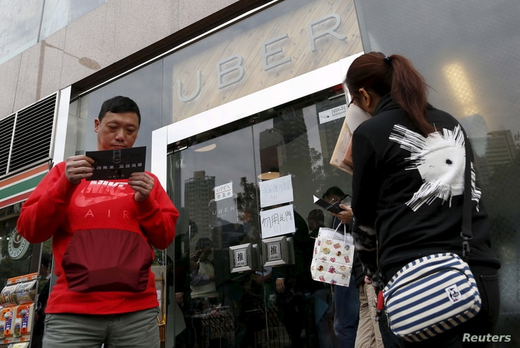 FILE - Drivers wait outside the office of taxi-hailing service Uber Inc. during a driver recruitment event in Hong Kong, China, Dec. 29, 2015.