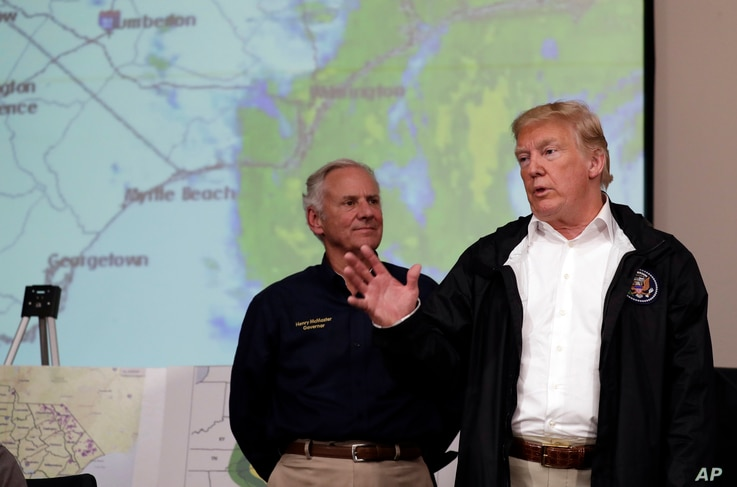 FILE - President Donald Trump speaks to first responders as he visits the Horry County Emergency Management center in the area impacted by Hurricane Florence, Sept. 19, 2018, in Conway, South Carolina, as the state's governor, Henry McMaster, listens...