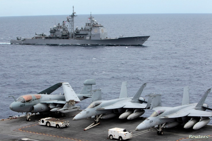 FILE - U.S fighter jets on standby at the upper deck of a USS George Washington aircraft carrier while the USS Cowpens passes by, in the South China Sea, 170 nautical miles from Manila, September 2010.