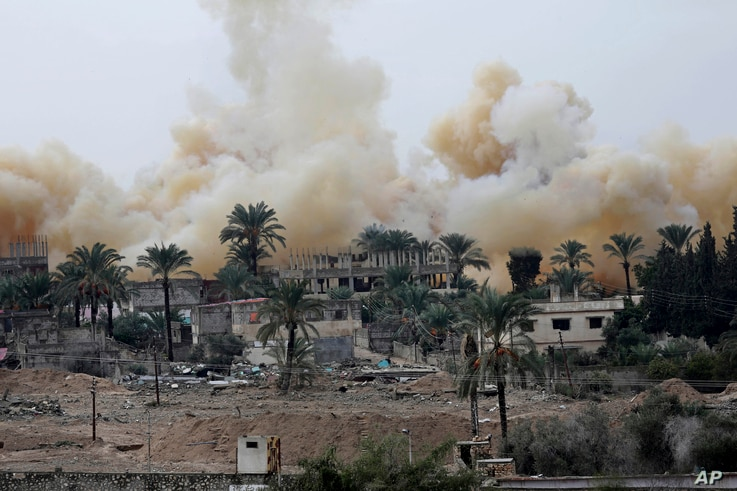 Smoke rises from explosions demolishing houses on the Egyptian side of the border town of Rafah as seen from the Palestinian side of Rafah in the southern Gaza Strip, Nov. 4, 2014.