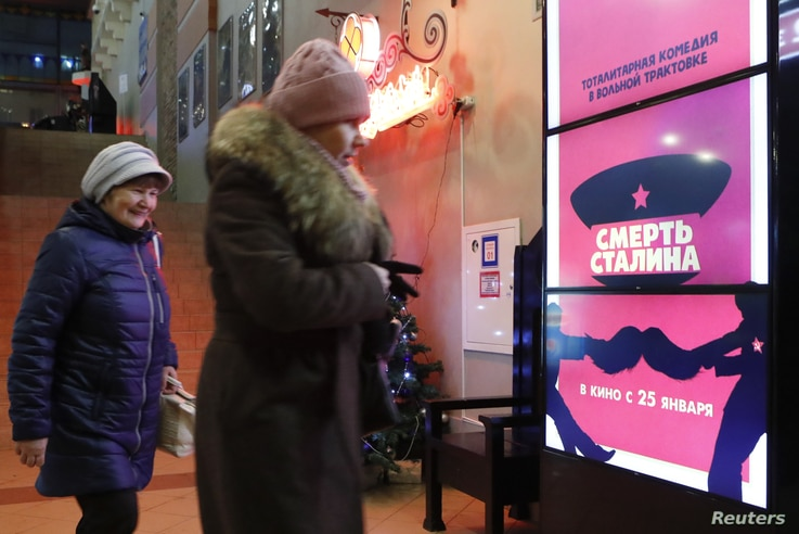 """People walk past a poster of the movie """"Death of Stalin"""" at a cinema in Moscow, Russia. Picture taken Jan. 22, 2018."""