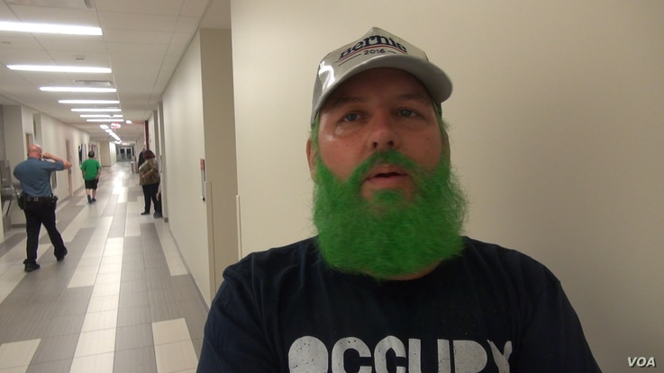 Ryan Trundle of Shreveport, La., a former Bernie Sanders delegate at the Democratic convention, wore a Bernie cap to the Green Party gathering in Houston and dyed his beard green to demonstrate his enthusiasm for Jill Stein. (G. Flakus/VOA)