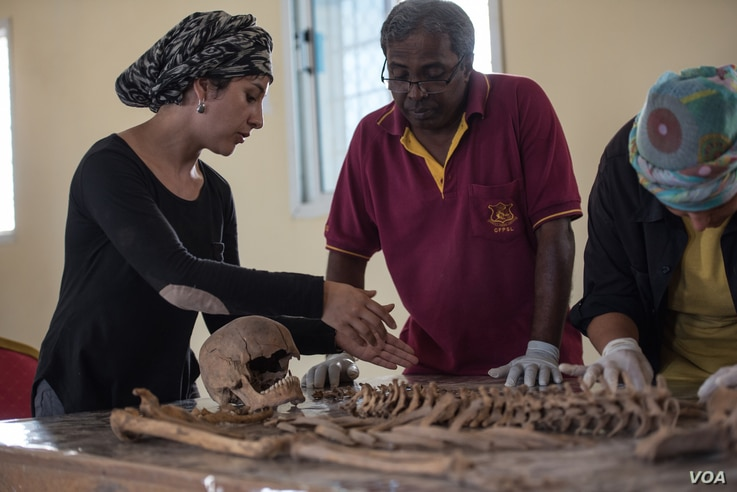 Valeska Martinez, left, and her colleagues analyze human remains — which appear to have suffered a gunshot wound to the head — in a lab in Berbera, Somaliland. (J. Patinkin/VOA)