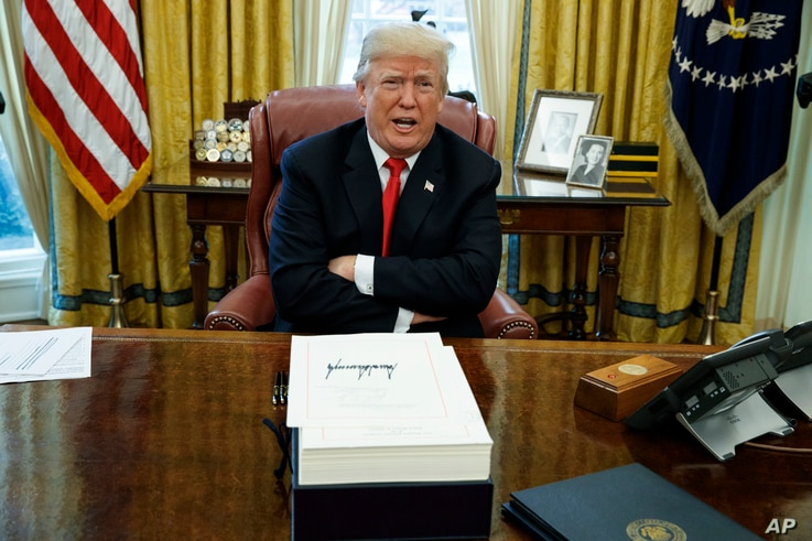 FILE - President Donald Trump speaks with reporters after signing the tax bill and continuing resolution to fund the government, in the Oval Office of the White House in Washington. For Trump, that energy-sapping 2017 cocktail of blistering president...