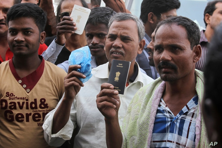 FILE - Foreign workers hold their passports as they gather outside a labour office, after missing a deadline to correct their visa status, in Riyadh, Nov. 4, 2013