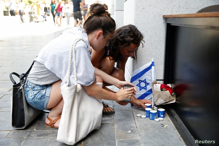 Israelis light candles near the site of a Palestinian shooting attack in Tel Aviv, June 9, 2016.