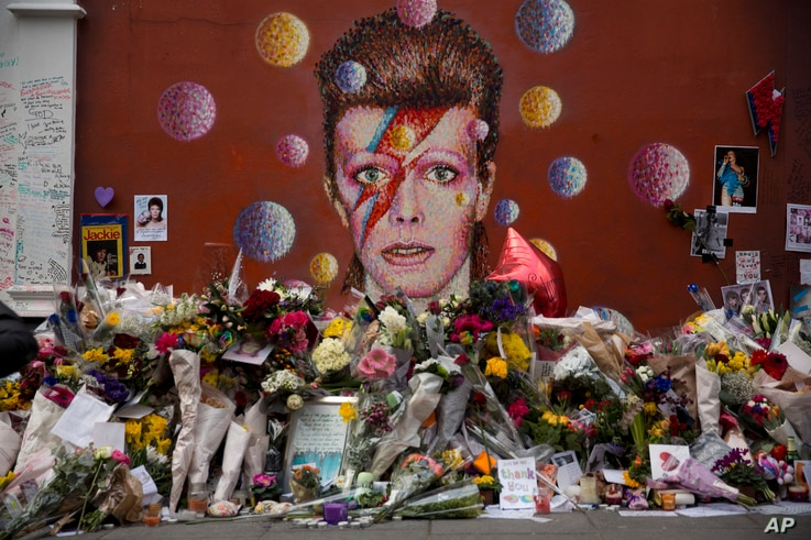 Tributes lie placed around a mural of British singer David Bowie by artist Jimmy C in Brixton, south London, Thursday, Jan. 14, 2016.