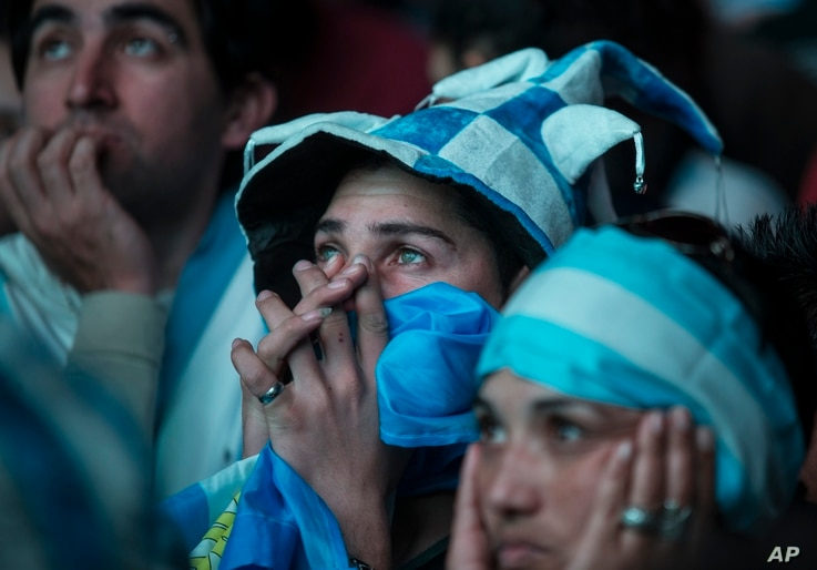 Argentina soccer fans react as they watch via a live broadcast the World Cup final match between Argentina and Germany on an outdoor television screen in Buenos Aires, Argentina, July 13, 2014.