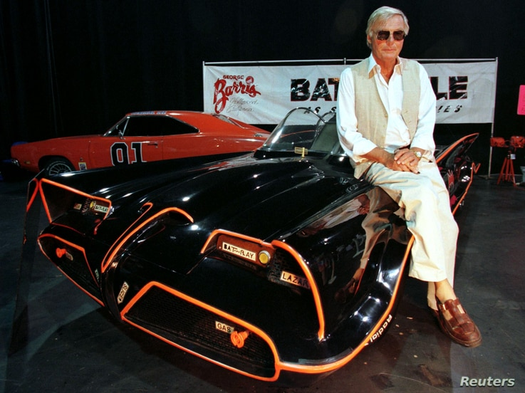 """FILE - Actor Adam West, who portrayed the title character in the 1960's television series """"Batman,"""" poses atop the original Batmobile used in the hit series."""