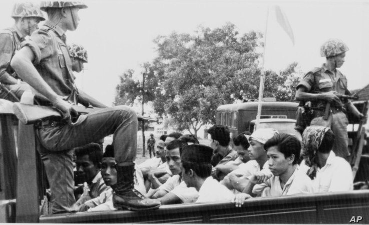 Members of the Youth Wing of the Indonesian Communist Party are guarded by soldiers as they are taken by an open truck to prison in Jakarta after they were rounded up by the army following a crackdown on communists after an attempted coup, Oct. 30, 1...