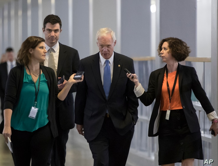 Sen. Ron Johnson, R-Wis., center, who has expressed opposition to his party's health care bill, walks to a policy meeting at the Capitol in Washington, June 27, 2017.