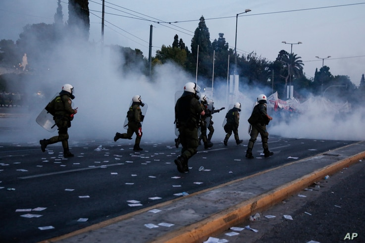 Policemen chase protesters during clashes in front of the parliament in Athens, May 8, 2016.