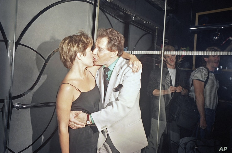 FILE - Carrie Fisher gives her father, Eddie Fisher, a happy birthday kiss at Stringfellow's in New York, Aug. 11, 1988. The daughter threw her father the party in honor of his 60th birthday.