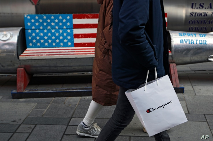 A couple carries a paper bag containing goods purchased from American brand Champion past a bench painted with the U.S. flag at the capital city's popular shopping mall in Beijing, Feb. 13, 2019.