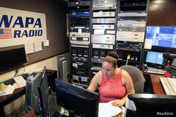 A woman works at the WAPA 680 radio station, in San Juan, Puerto Rico, Sept. 27, 2017.