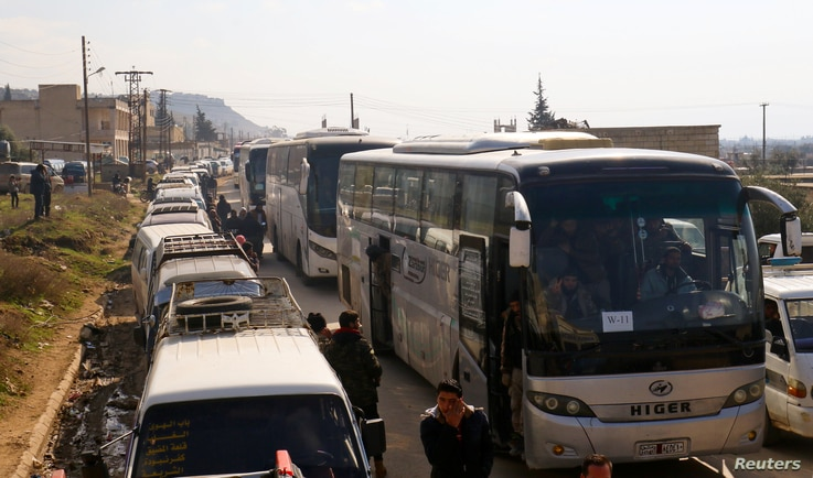 Civilians and rebel fighters are evacuated from the Wadi Barada valley after an agreement was reached between rebels and Syria's army, arrive riding buses in the rebel controlled Qalaat al-Madiq, Syria, Jan. 30, 2017.