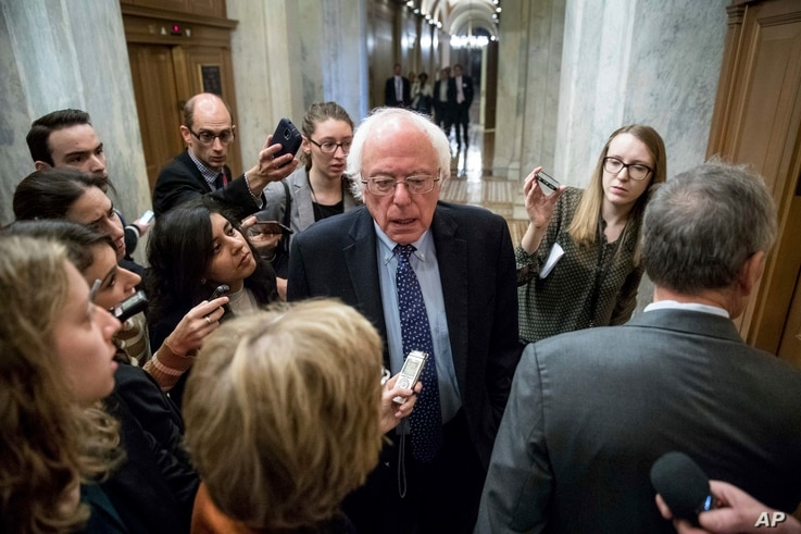 Sen. Bernie Sanders, I-Vt., center, speaks to reporters on Capitol Hill in Washington.