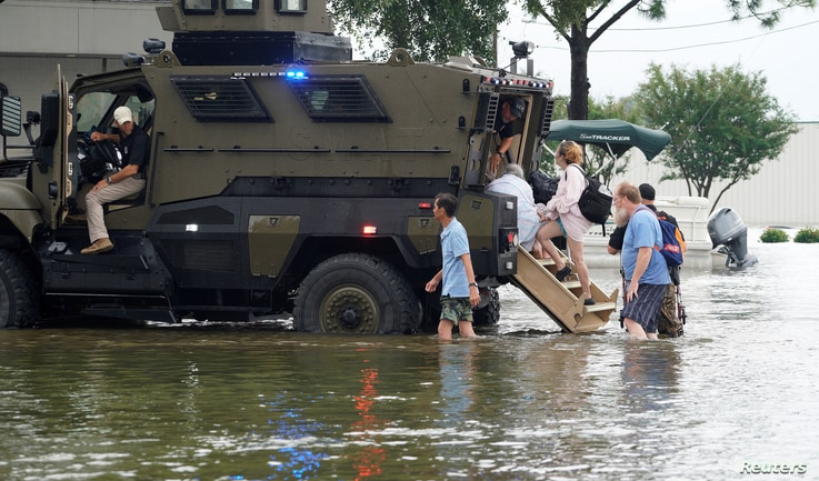 People are rescued from floodwaters from Hurricane Harvey in an armored police mine-resistant ambush protected (MRAP) vehicle in Dickinson, Texas, Aug. 27, 2017.