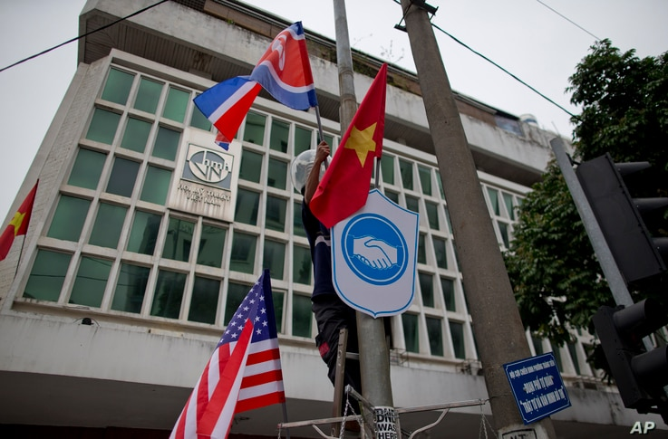 A man installs flags of North Korea, the U.S and Vietnam on a post in a street neighboring Government Guesthouse and the Metropole hotel ahead of the North Korea-U.S. summit in Hanoi, Vietnam, Feb. 25, 2019.