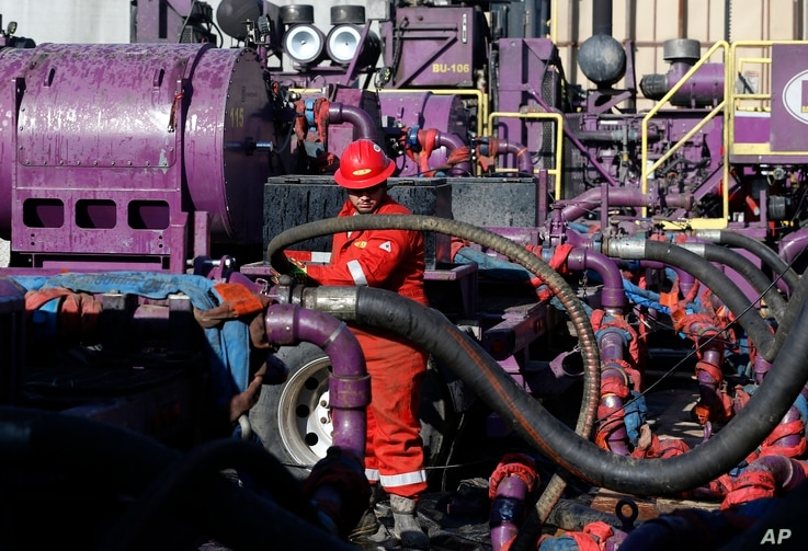 FILE - In this March 25, 2014 file photo, a worker adjusts hoses during a hydraulic fracturing operation at a gas well, near Mead, Colorado.