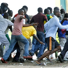 Supporters of Congolese opposition leader Etienne Tshisekedi run as riot police charge with tear gas and live fire outside their candidate's headquarters in Kinshasa, Democratic Republic of Congo, December 8, 2011