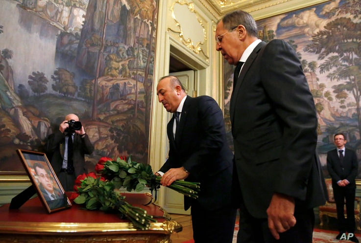 Russian Foreign Minister Sergey Lavrov, right, and Turkey's Foreign Minister Mevlut Cavusoglu offer flowers in memory of Russian Ambassador to Turkey, Andrei Karlov, who was in Ankara, Turkey, Dec. 20, 2016.