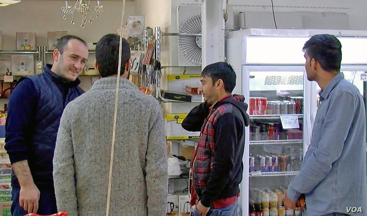 Afghan migrants chat with a Turkish employee at a Halal supermarket in Reims.