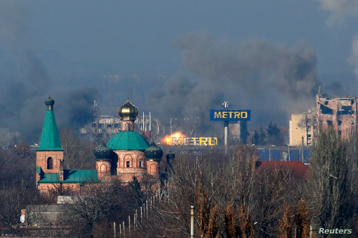 Smoke rises above an old terminal, left, and an administrative building of the airport after the recent shelling during fighting between pro-Russian separatists and Ukrainian government forces in Donetsk, eastern Ukraine, Nov. 9, 2014.