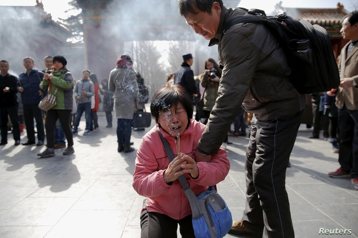A crying woman falls on her knees as relatives of passengers onboard of Malaysia Airlines flight MH370 which went missing in 2014, burn incense sticks and pray at Lama Temple in Beijing, China, March 8, 2016.