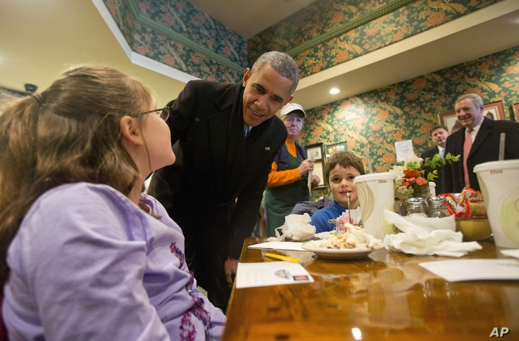 President Barack Obama, accompanied by Senate Minority Whip Richard Durbin of Illinois, right, stops to greet Anna Moser, 9, and brother Grant Moser, 6, right, during an unscheduled stop to the Feed Store, a sandwich shop in Springfield, Ill., Feb. 1...