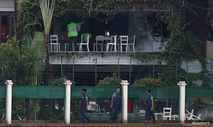 Policemen patrol outside the Holey Artisan Bakery and the O'Kitchen Restaurant as others inspect the site after gunmen attacked, in Dhaka, Bangladesh, July 3, 2016.