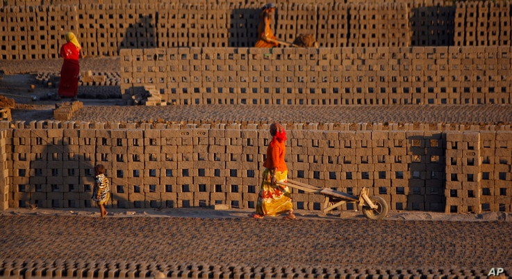 Women laborer transport bricks on hand carts at a brick kiln factory on the outskirts of Jammu, India, Nov. 26, 2013.