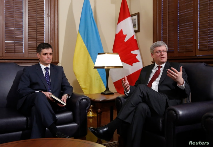 Canada's Prime Minister Stephen Harper (R) speaks during a meeting with Ukraine's Ambassador to Canada Vadym Prystaiko in Harper's Langevin Block office in Ottawa March 17, 2014.