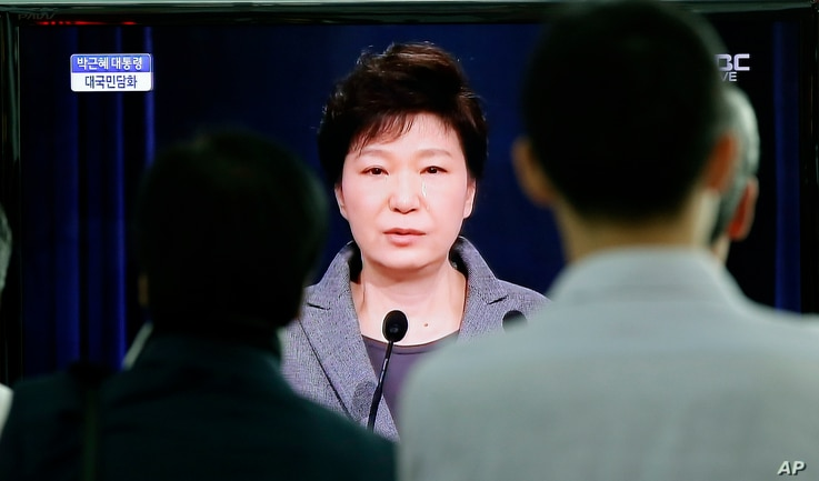 People watch a live television program showing South Korean President Park Geun-hye's speech to the nation regarding the sunken ferry Sewol at the Seoul Train Station in Seoul, South Korea, Monday, May 19, 2014.