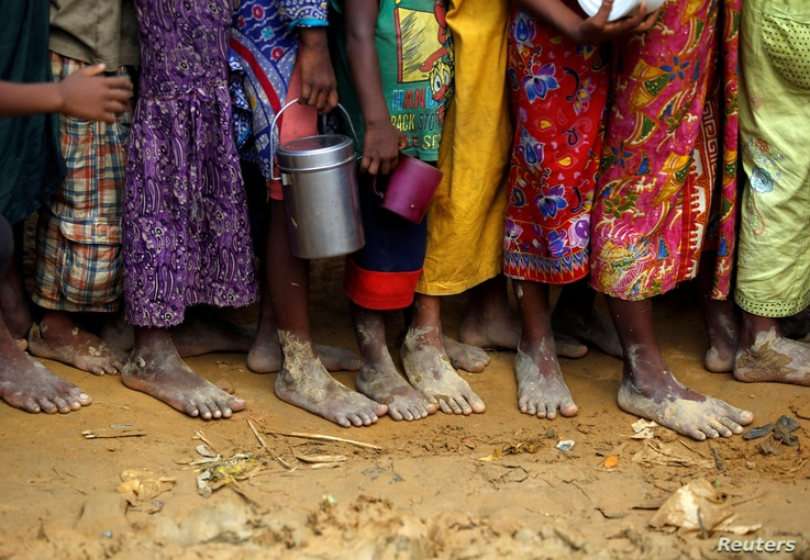 Bare feet of Rohingya refugee children are pictured as they stand in a queue while waiting to receive food outside the distribution center in Palongkhali makeshift refugee camp in Cox's Bazar, Bangladesh, Nov. 7, 2017.