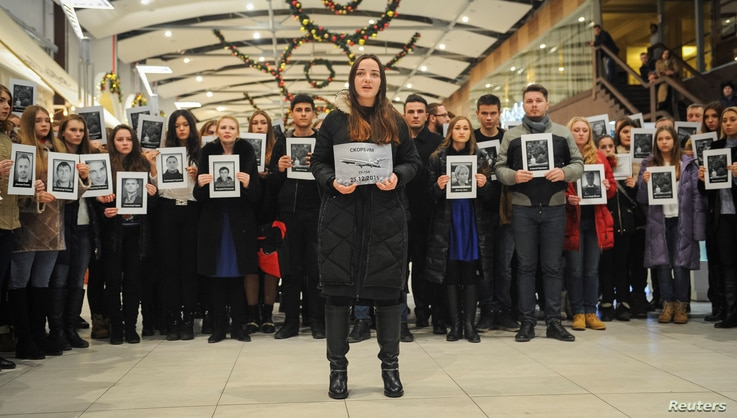 People hold portraits and printed names of victims of the Tu-154 plane, which crashed into the Black Sea on its way to Syria on Sunday, during a memorial event in Rostov-On-Don, Russia Dec. 26, 2016.